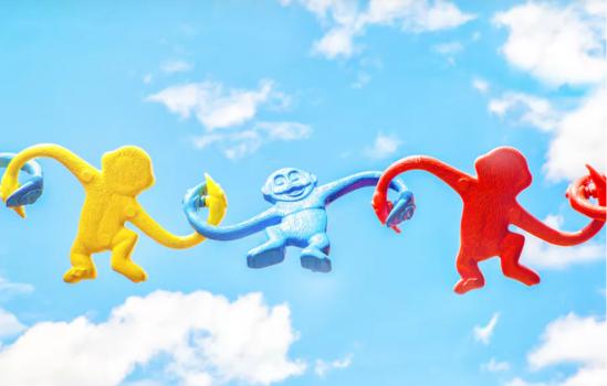 plastic monkeys holding hands in sky