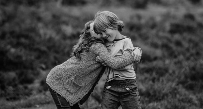 black and white image of young children hugging