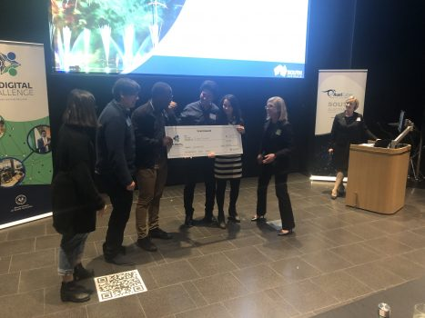 students holding cheque