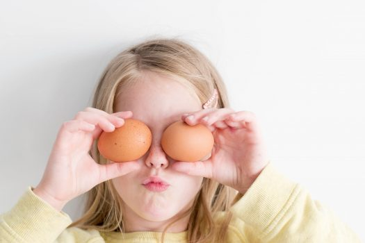 girl holding eggs in front of her eye